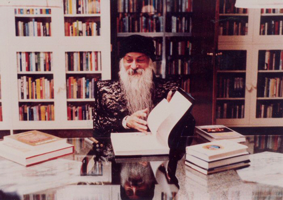Osho signing books in his library