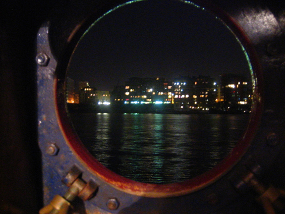 London lights through a porthole of the Volharding, moored on the Thames