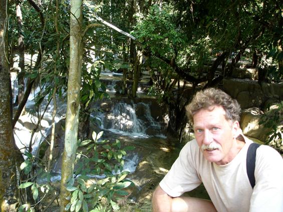 Premesh in Laos sitting ata waterfall