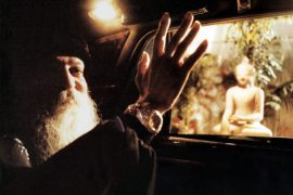 Osho waving past Buddha statue