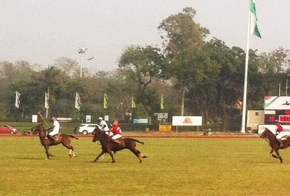 Galloping: With mallets in the air, players chase the ball for a goal with the scoreboard on the right.