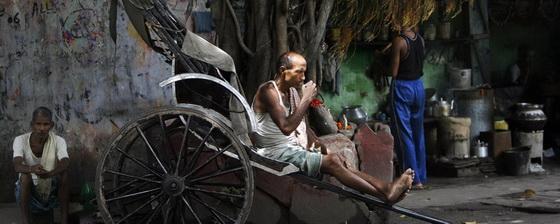 An Indian rickshaw puller sips tea while