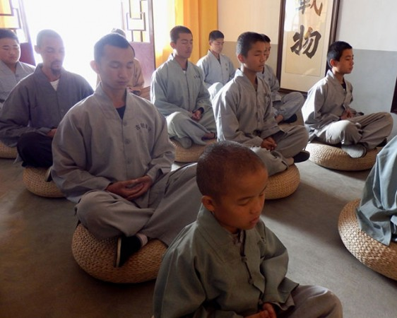 Students meditating in front of an altar dedicated to Bodhidharma