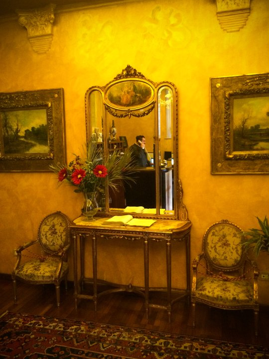 Reflection: Hotel Noblesse, Lucca, Italy - The receptionist was making a call and from where I was standing it looked like a painting.