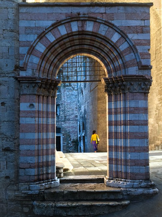 Morning Light: Perugia, Italy - I turned around and saw this woman framed in the arch, catching the morning light. Her colours matched perfectly.