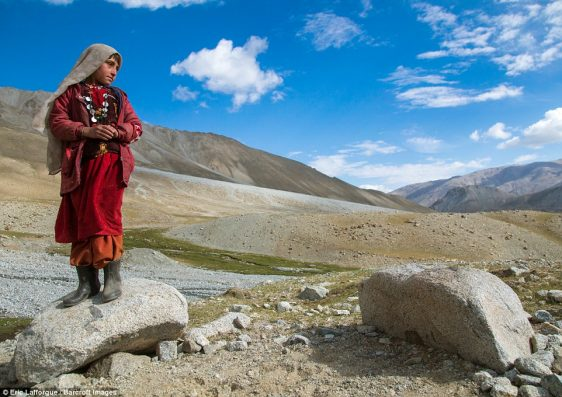 Wakhi nomad girl stands on a rock as she overlooks the harsh, desolate terrain between Tajikstan and Pakistan