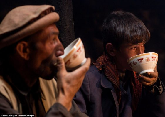 Two Afghan men sip soup from a bowl