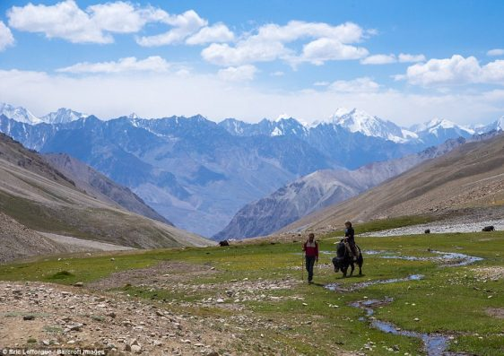 A man and woman take to the trek trail in the Pamir mountains with yaks