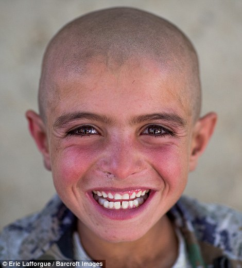 Young boy with a shaved head grins eagerly for photographer Eric Lafforgue, the first tourist of the year