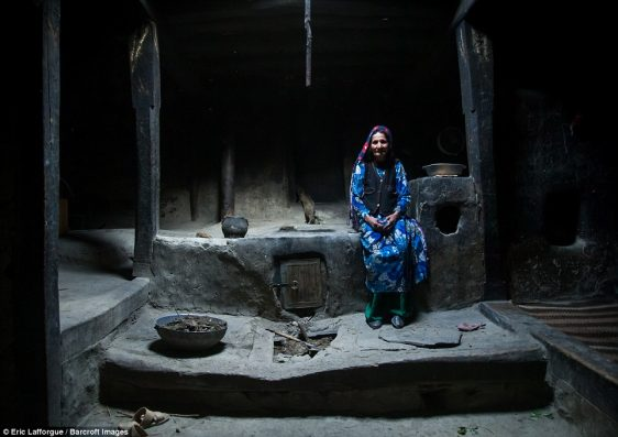 Afghan woman in vibrant blue and green, inside her traditional Pamiri house, which is simply put together without luxuries