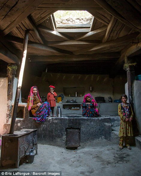 Afghan family inside their traditional Pamiri house
