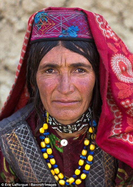 Portrait of a Wakhi nomad woman, dressed in a bright headscarf with yellow and blue beads around her neck