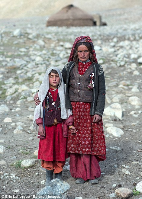 Nomad woman with her daughter, dressed in layers with boots to cope with the terrain