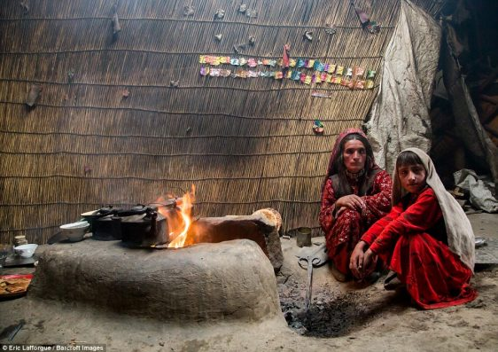 Wakhi nomad family inside a yurt, where they prepare food and hot drinks on an open flame with a pit for fuel and ashes