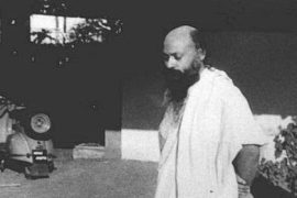Osho standing in courtyard Feat