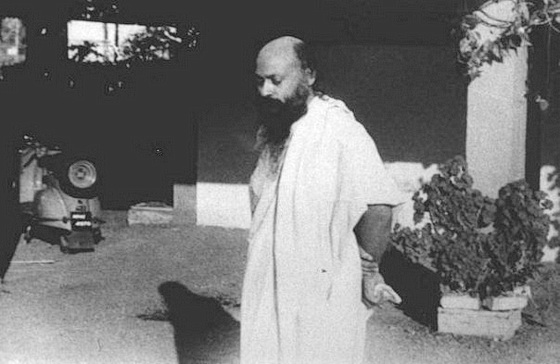 Osho standing in courtyard
