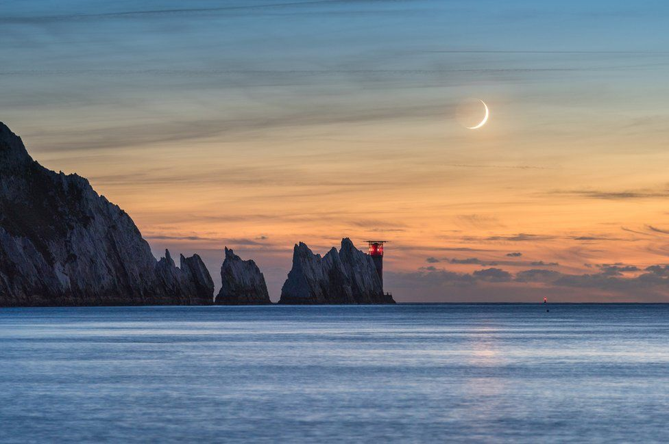 Ainsley Bennett captures the waxing crescent Moon setting in the evening sky over the Needles Lighthouse on the western tip of the Isle of Wight
