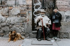 Old couple sitting outside an old house