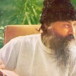 Osho with book in garden