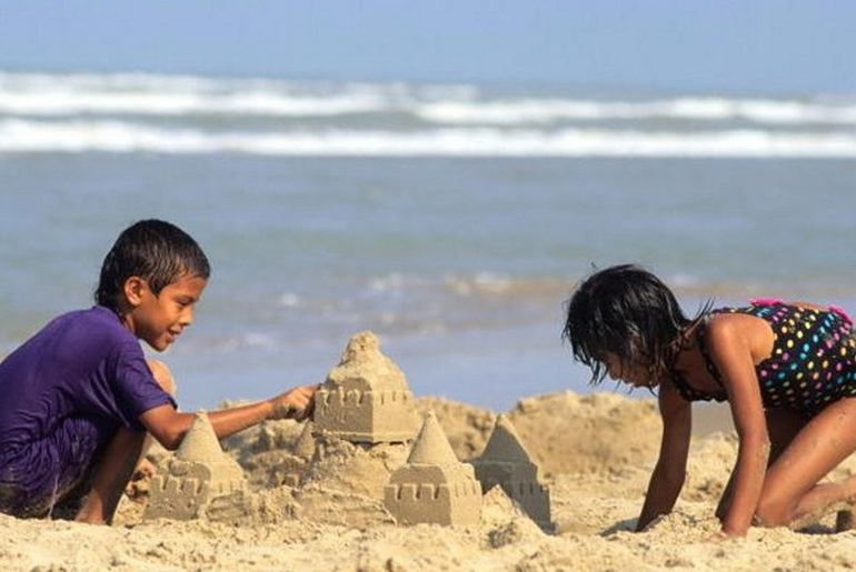 Buddha watches children play with sandcastles