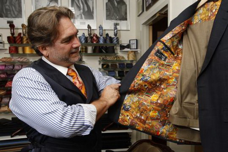 tailor looking at the inside of a coat