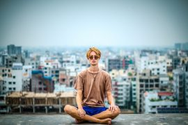 Young man meditating on roof