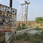 A rusty signboard featuring Osho on the main road leading to the village