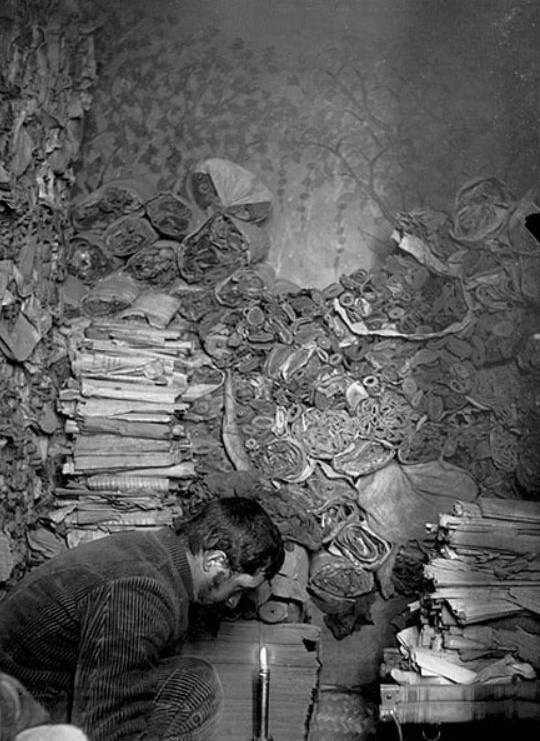 Paul Pelliot selecting manuscripts in the 'Library Cave' in 1908