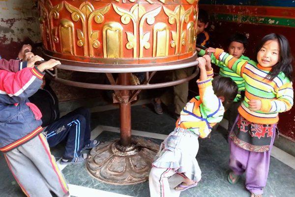 children playing on prayer drum